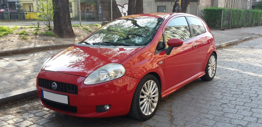 Used, red Fiat Grande Punto Sporting on 17 inch OEM wheels, stylish 3-door hatchback