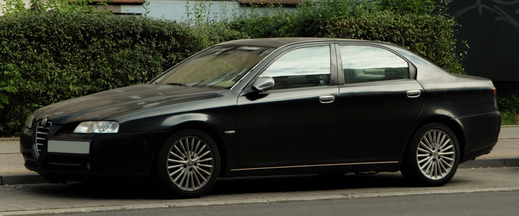 Used, black Alfa Romeo 166 on OEM alloy wheels. A post-facelift model.