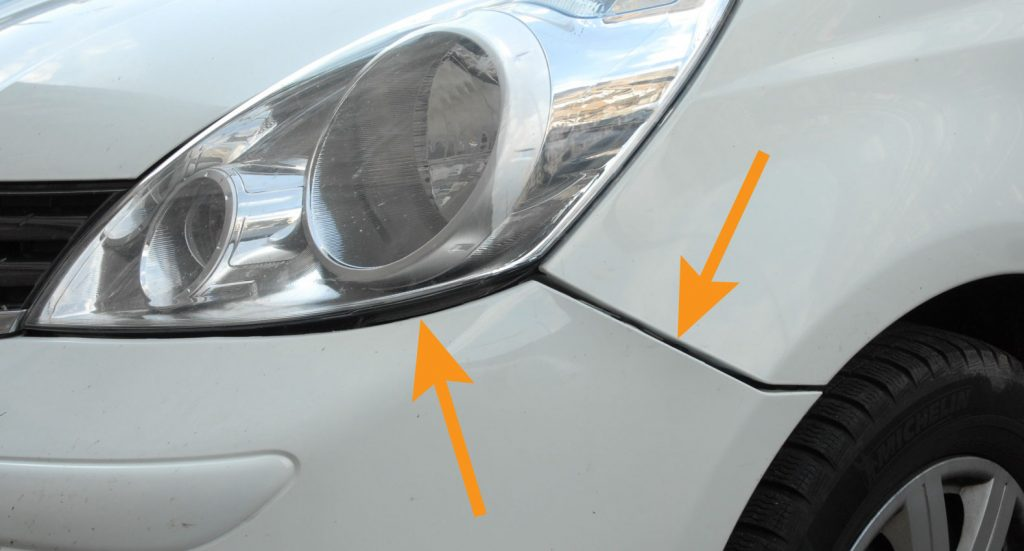 Poorly attached front bumper on a white car. Large and uneven panel gaps pointed out with arrows.