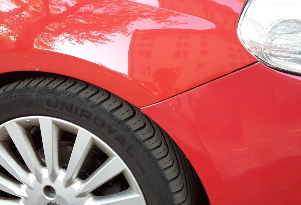 Front fender of a used, red Fiat car. There is a visible colour mismatch between the fender and the bumper.