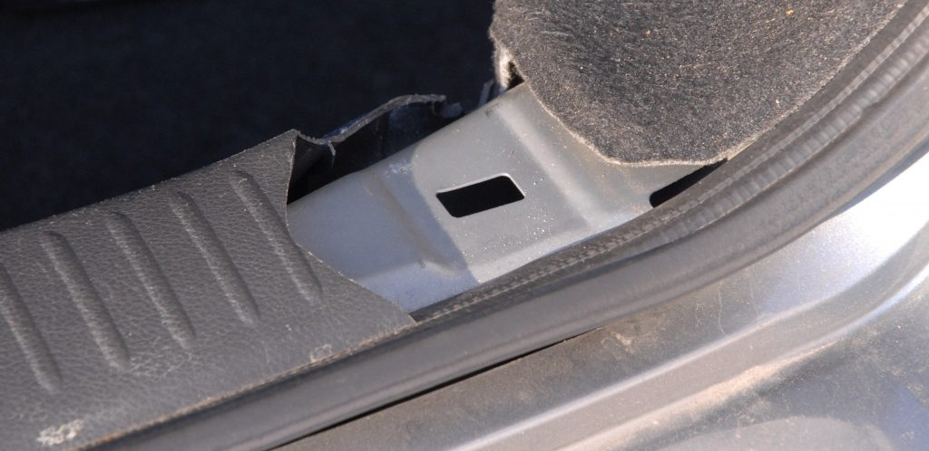 Cracked plastic cover next to the boot seal in a used, grey car.
