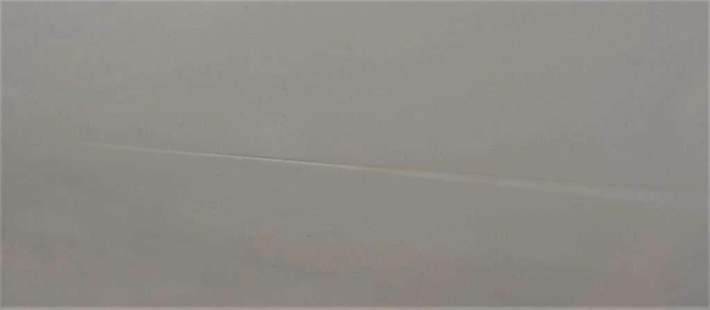 A paint scratch on a white, used car. The scratch penetrated the paint but not the primer. The metal is not visible.