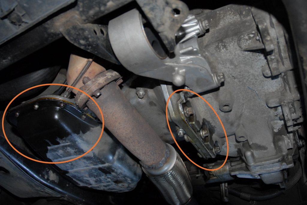 Underside view of the engine and transmission in a used car. The oil pan and engine bell housing are wet with oil.