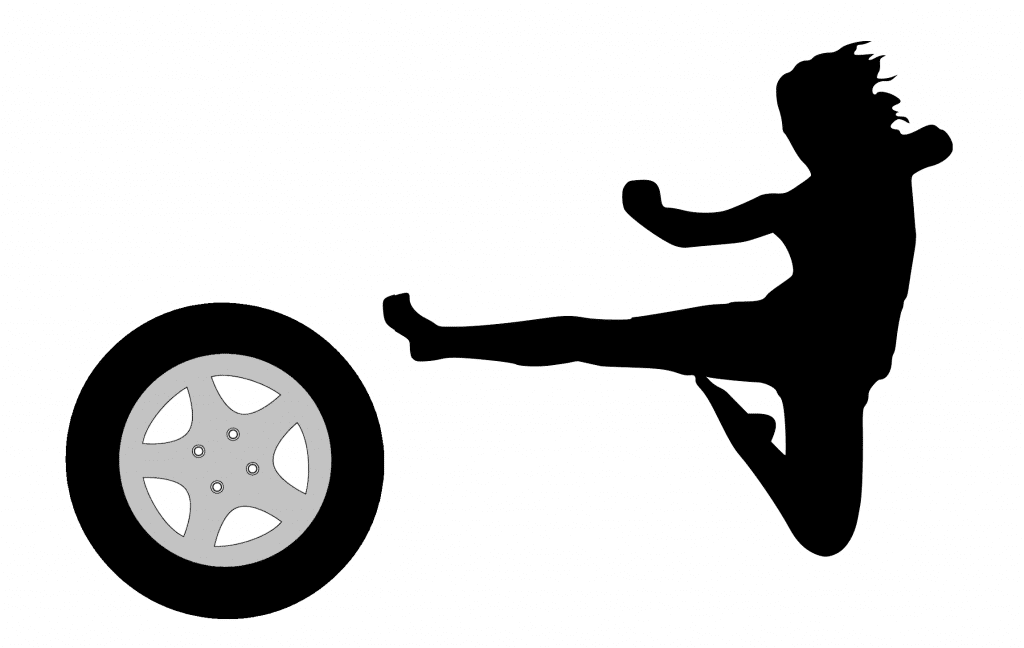 Silhouette of a man kicking a tyre.
