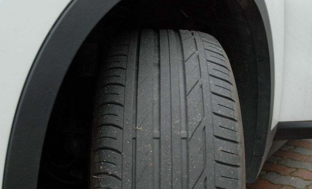 Front tyre on a used, white car. Tyre tread is worn evenly.