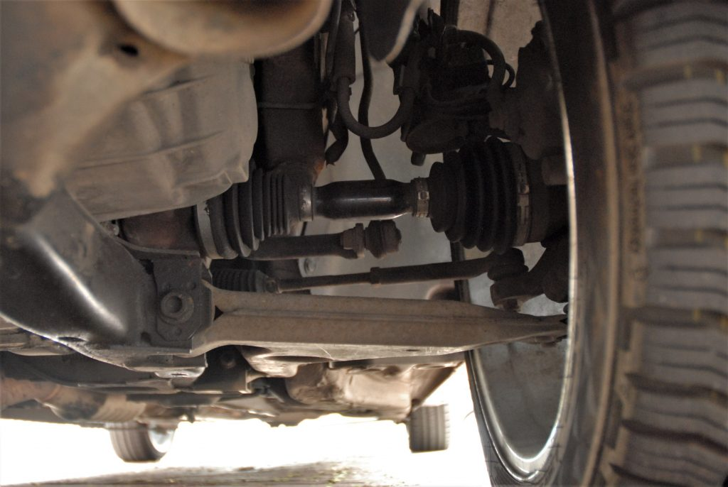 Underside view of the front suspension in a used car. The axle shaft and both CV joints are visible.