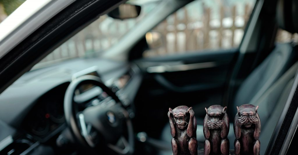 a small statute of three monkeys in a car
