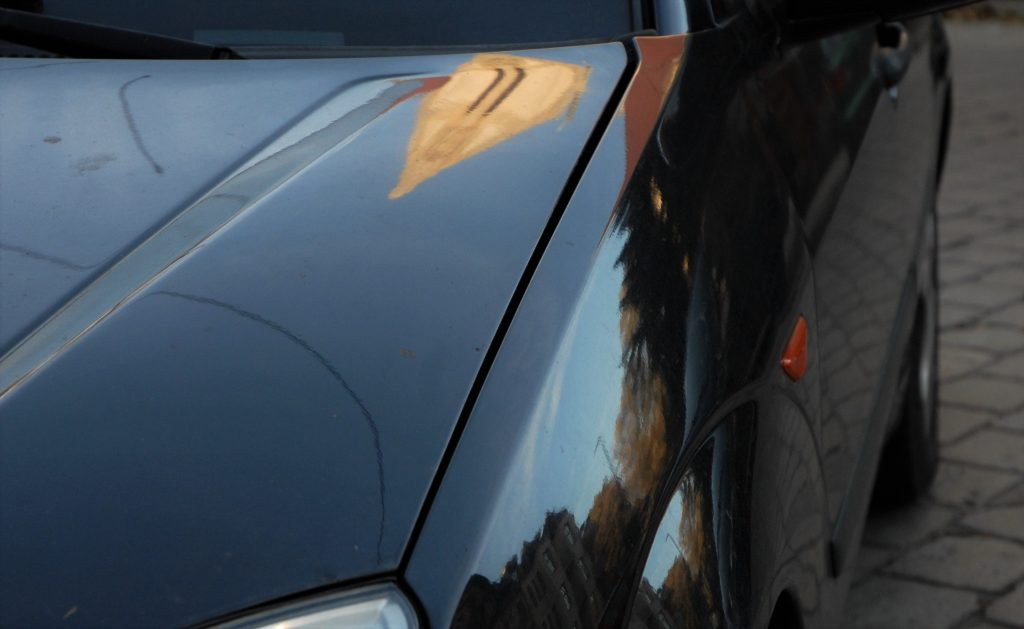 Uneven panel gap between the bonnet and the front wing on a used car. The gap becomes narrower towards the headlight.