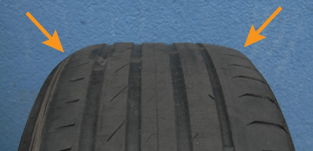 Worn-out car tyre. The tread is unevenly worn.