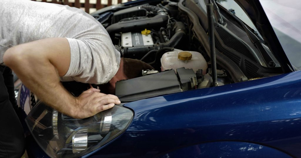 A man with his head deep inside the engine bay inspecting a used car for problems