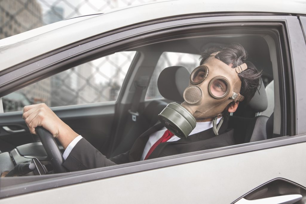 A man driving with a gas mask.