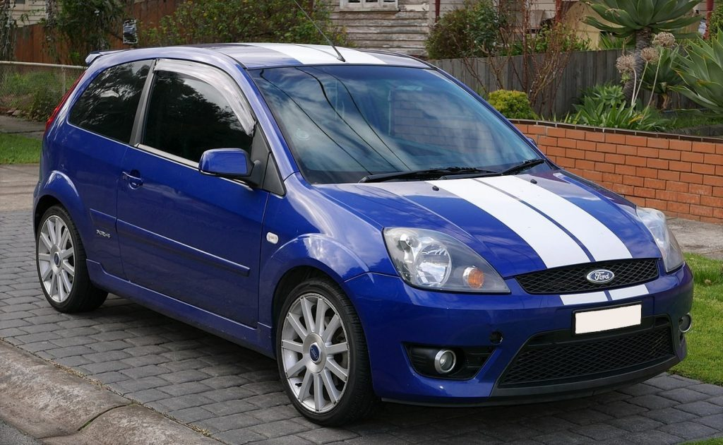 Used, blue Ford Fiesta ST (Mk5) with white racing stripes and OEM alloy wheels.