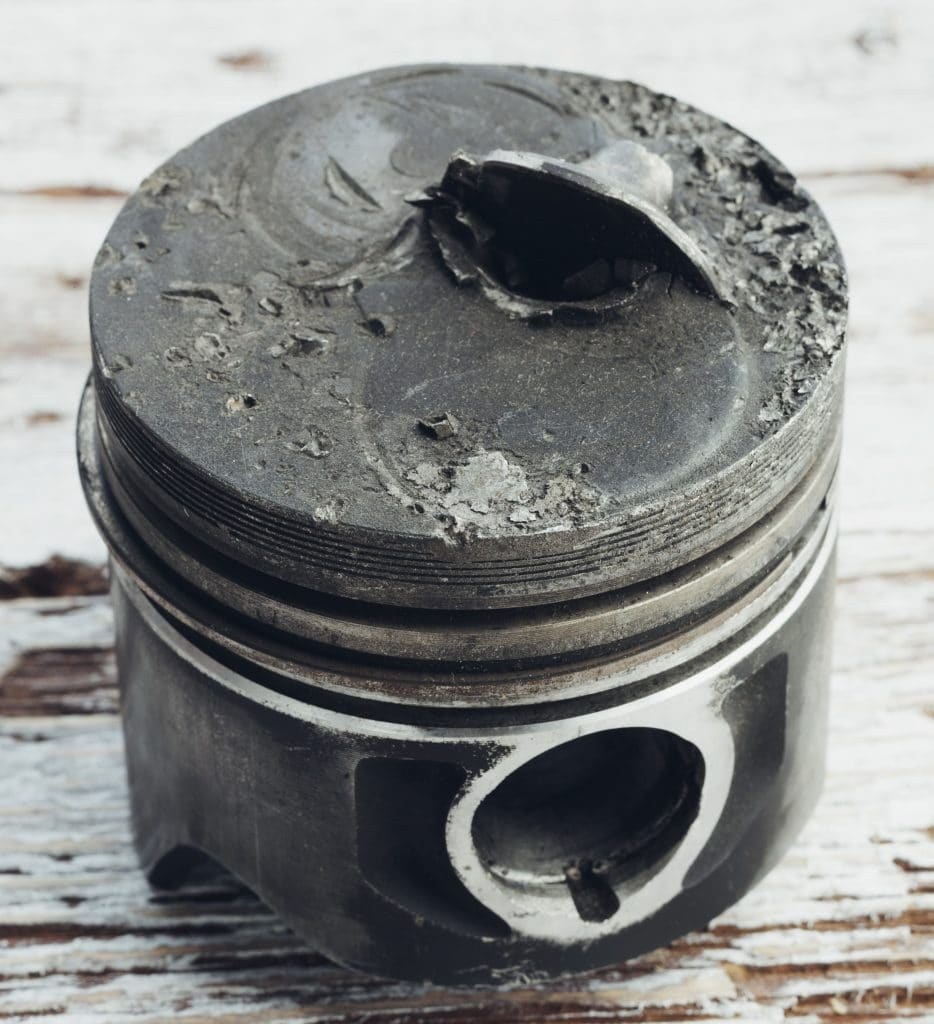 Badly damaged engine piston with a piece of the valve embedded in the piston crown.
